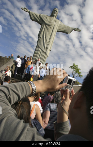 Tourists photograph themselves in front of the statue of Christ the Redeemer, Corcovado Mountain, Rio De Janeiro, - Stock Photo