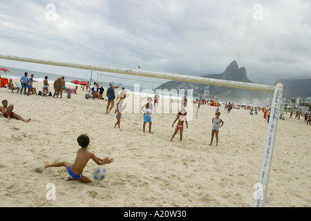 Brazilian children playing football on Copacabana beach, Rio De Janeiro, Brazil, South America - Stock Photo