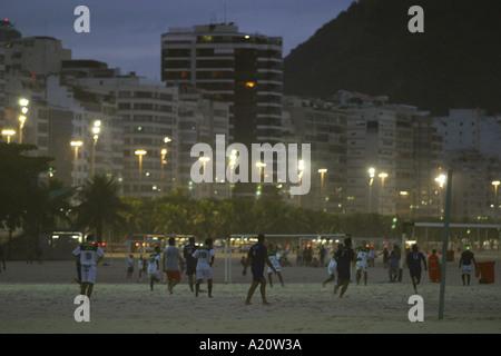 Men playing football on Copacabana beach in the evening, Rio De Janeiro, Brazil, South America. - Stock Photo