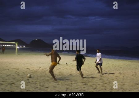 Men playing football on Copacabana beach in the evening , Rio de Janeiro, Brazil. - Stock Photo
