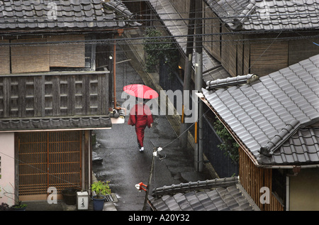 woman wearing a red kimono and carrying a red umbrella walks through rain in the old streets of Gion district of - Stock Photo