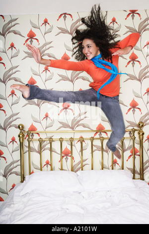 Teenage Girl, arms outspread, kicking, jumping on bed - Stock Photo