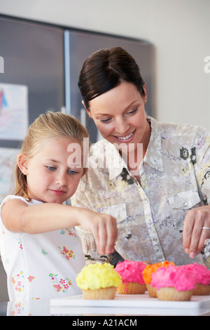 girl decorating cupcakes in kitchen mother and daughter decorating cupcakes in kitchen stock photo