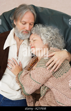 Couple Cuddling in Chair - Stock Photo