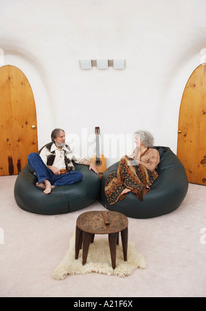 Couple Sitting in Bean Bag Chairs in Living Room - Stock Photo