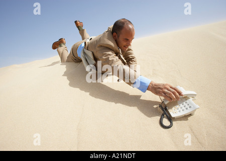 Businessman Reaching for Telephone in Desert - Stock Photo