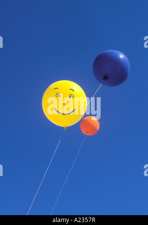Smiley Face  Balloons Floating Against a Blue Sky - Stock Photo