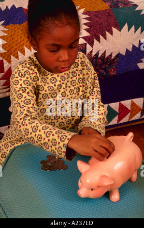 6 year old African American girl putting coins in piggy bank - Stock Photo