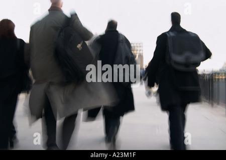 crowds of people commuters on London Bridge walking to work - Stock Photo