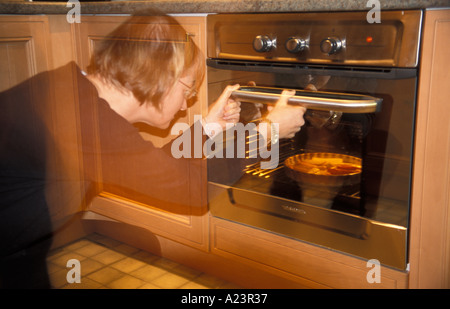 Woman checking a meal in the oven - Stock Photo
