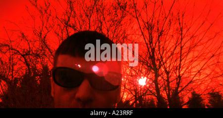 red weird man male sunlight alien sinister trees branches crimson scarlett colour color horizontal light refraction - Stock Photo