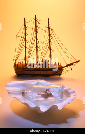 Ship Model and Ship in a Bottle on Seashell - Stock Photo