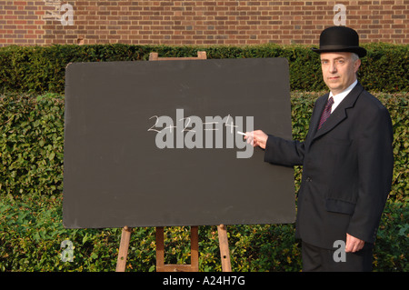 City gent in suit and bowler hat explaining simple maths with traditional chalk and blackboard. 2+2 = 4. Two plus - Stock Photo