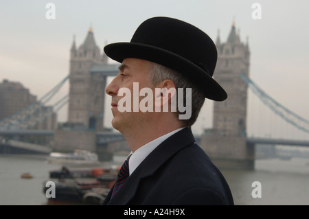 Traditional British city gent in bowler hat and business suit by Tower Bridge, London, UK - Stock Photo