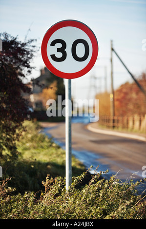 Road sign - 30mph speed limit at edge of small village, England, UK - Stock Photo