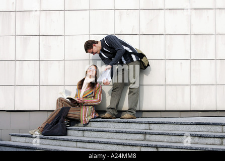 Girl and Boy Talking on Stairs - Stock Photo