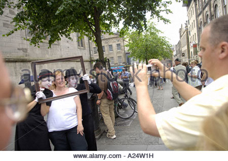 Street Performers being photographed   with tourist on the The Royal Mile at the Edinburgh Festival - Stock Photo