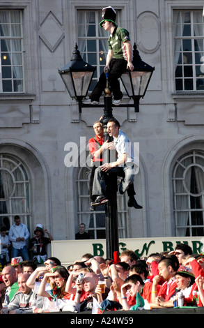 Rugby fans climb lamp post outside Cardiff City Hall South Wales UK - Stock Photo