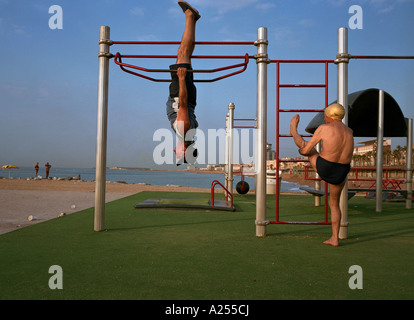 Two Spanish gentlemen exercise on the beach near Port Olympic in Barcelona Spain - Stock Photo