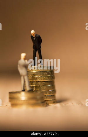 Miniature businessmen standing on coins on financial newspaper - Stock Photo