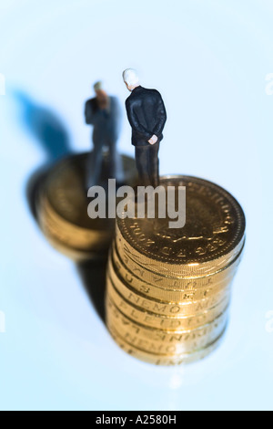 Miniature businessmen standing on coins - Stock Photo