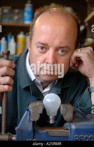 AN ELECTRICAL SHOP OWNER IN HIS WORKSHOP WITH A LIGHT BULB IN A VICE UK - Stock Photo