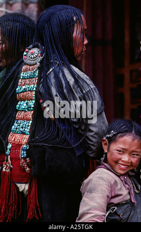 Young girl stands behind her mothers 108 braids beautiful coral turquoise hair piece Sera Monastery Lhasa Tibet - Stock Photo