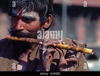 A SHAIVITE SADHU or Hindu follower of Shiva plays flute at the Hindu Temple complex of PASHUPATINATH KATHAMANDU - Stock Photo
