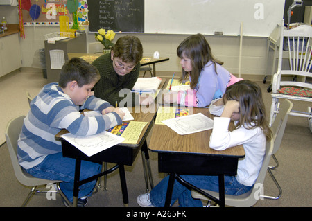 3rd grade elementary students working in group helping each other - Stock Photo