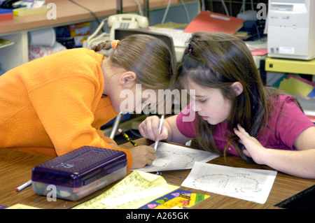 3rd grade elementary students working together in group helping each other - Stock Photo