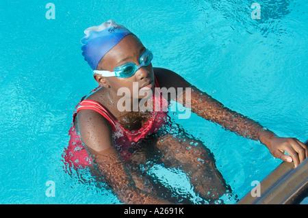 African american minority female participating participate in a swim swimming backstroke race - Stock Photo