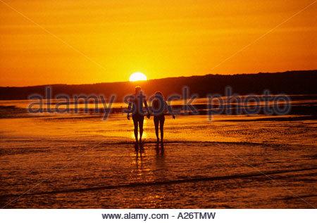 A couples romantic hand in hand walk into the  sunset Sandy Beach Puerto Penasco Mexico - Stock Photo