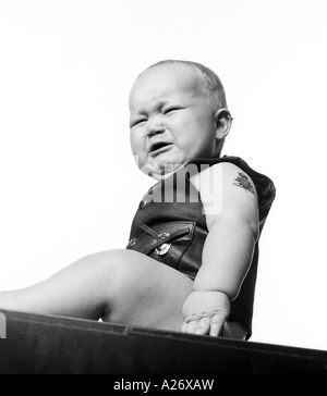 Baby boy (6 months) wearing leather vest. - Stock Photo