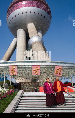 Two chinese monks as tourists in front of the Oriental Pearl Tower, Pudong, Shanghai, China - Stock Photo