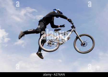 Biker performs tricky jump in the air - Stock Photo
