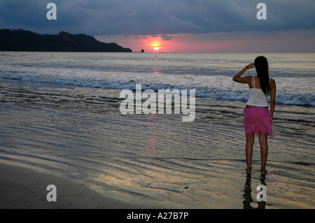 Girl observing Sundown on Brasilito Beach, Guanacaste Province, Costa Rica, Central America - Stock Photo