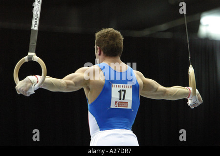 Italian male Gymnast Matteo Morandi on the rings holding the crucifix position - Stock Photo