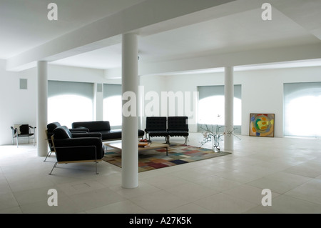 Living area with black seating and interior columns in minimalist warehouse conversion - Stock Photo