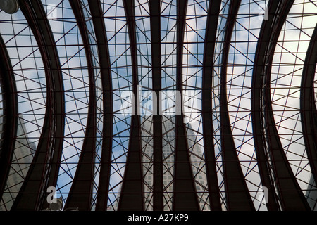 Office buildings in the Canary Wharf complex seen through the roof of the Canary Wharf train station - Stock Photo