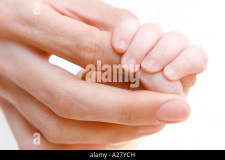 Baby haelt den Finger der Mutter, Baby holding hands with mother - Stock Photo