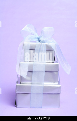 Stack of silver wrapped presents on a purple background - Stock Photo