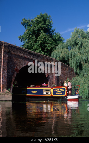 Couple steering traditional narrowboat beneath Sonning Bridge on the River Thames, Sonning, Berkshire, England - Stock Photo
