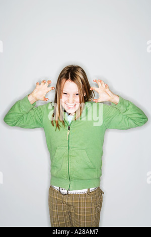 PORTRAIT OF 11 YEAR OLD GIRL WITH HANDS UP GRIMACING - Stock Photo