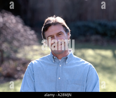 Middle-aged man in garden, smiling, Berkshire, England, United Kingdom - Stock Photo