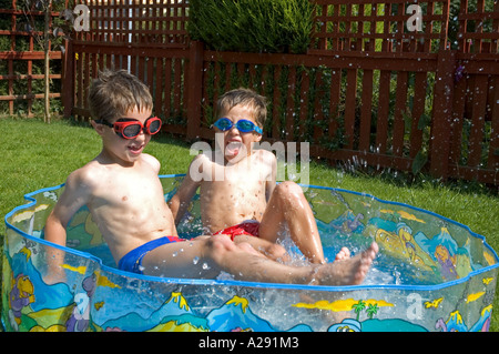 two little boys playing in a paddle pool - Stock Photo