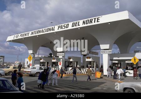 People and vehicles move toward the border and customs checkpoint on Avenida Juarez in Ciudad Juarez Mexico - Stock Photo