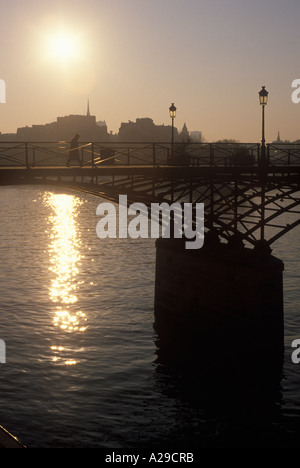 Man crossing Pont des Arts over river Seine Paris France Europe - Stock Photo