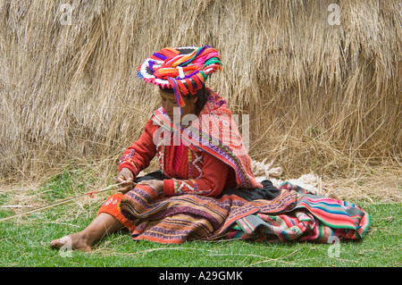A Peruvian woman dressed in traditional clothes demonstrating fabric weaving. - Stock Photo