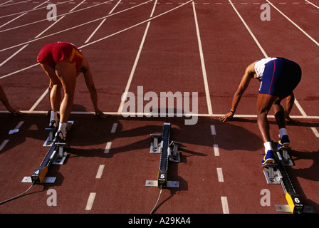 View from behind two male athletes in their blocks on the track at the start of a sprint race - Stock Photo