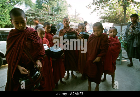 Myanmar northern Burma young buddhist monks on morning alms round - Stock Photo